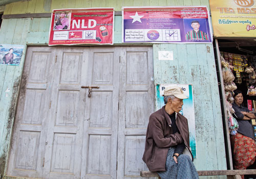 A man sits outside a small shop beneath election posters in Chin State in the run-up to last year's polls. Photo: Aung Myin Ye Zaw / The Myanmar Times
