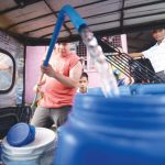 Muntinlupa City residents fill up plastic containers with water from artesian wells due to a two-week water supply shortage in many parts of the city. (Jansen Romero)